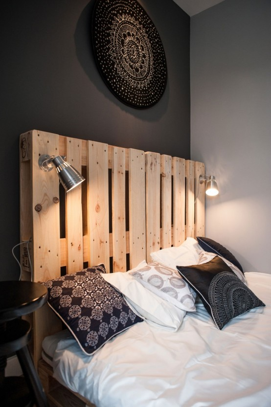 Chambre avec des murs noirs et une tête de lit en palette