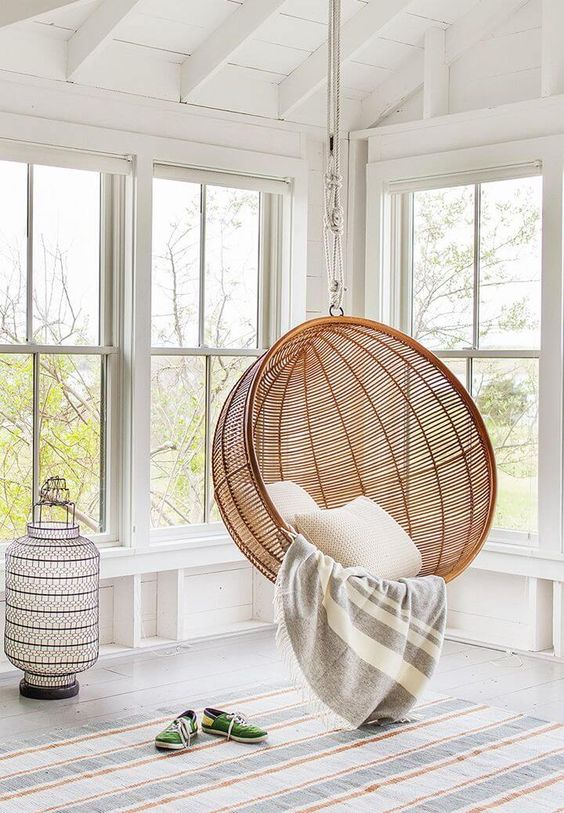 mobilier-rotin-fauteuilsuspendu-style-balancoire-lanterne-orientale-tapis-raye-coussins