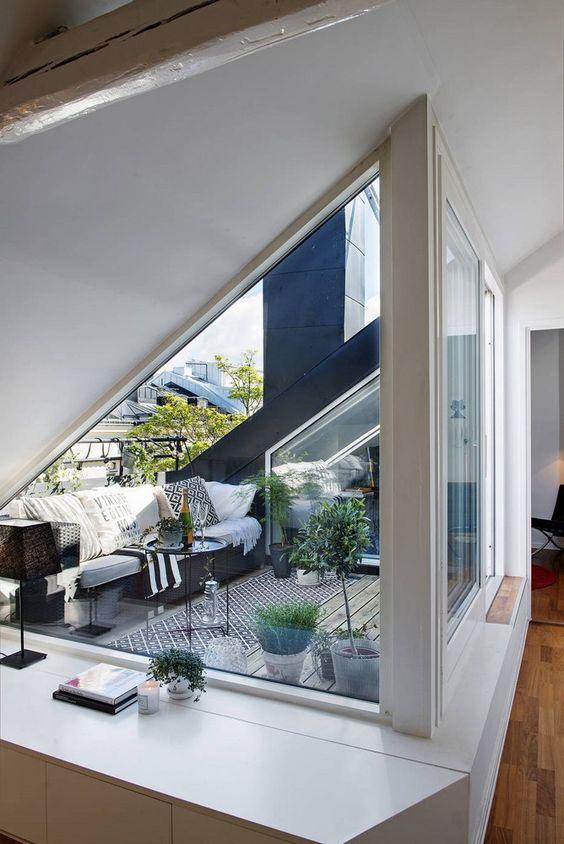 amenager-terrasse-loggia-sol-planches-bois-canape-coussin-tapis-imprime-geometrique-plantes-vertes
