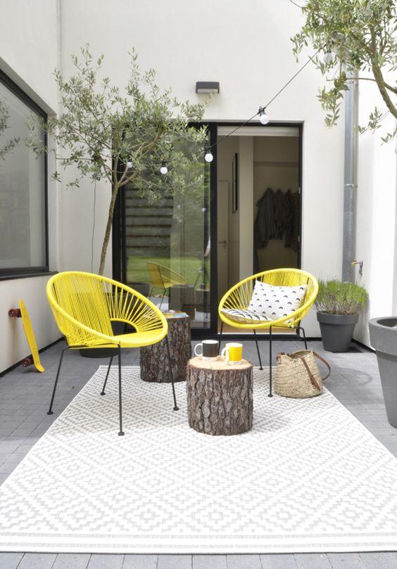 amenager-terrasse-tapis-imprime-geometrique-chaises-cordes-jaune-vif-table-basse-tronc-arbre-guirlande-ampoules-olivier
